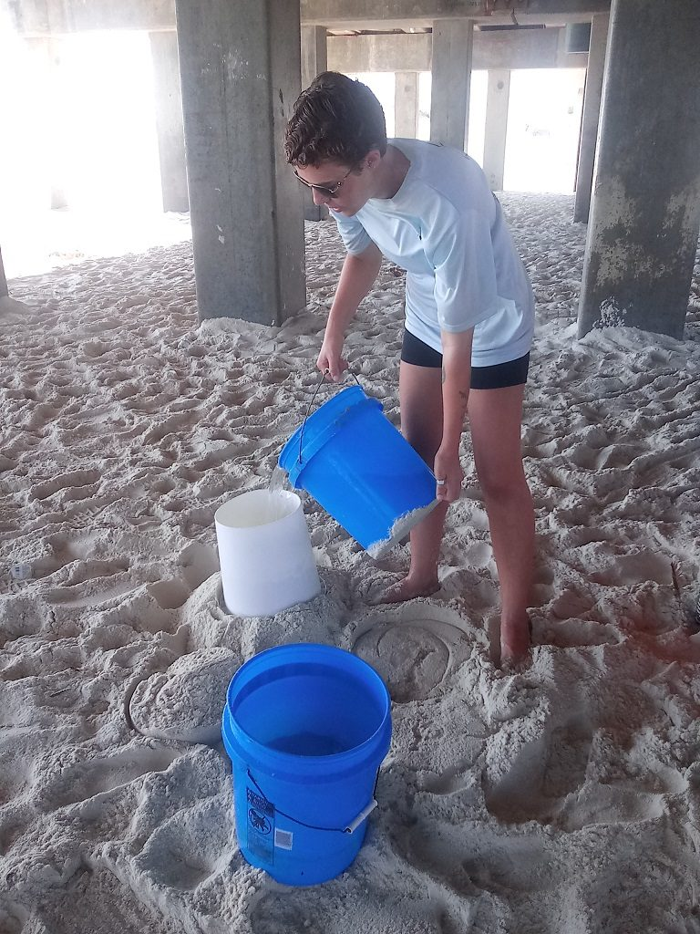 Buckets of water are added to fluffy sand